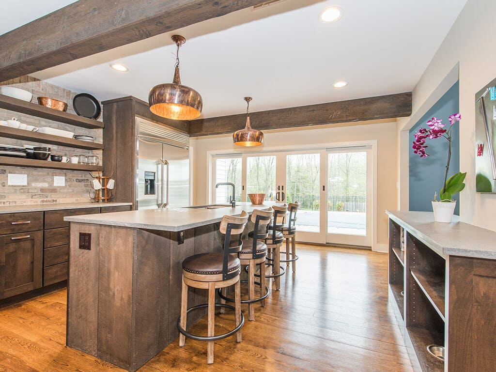 Rustic open floor plan kitchen, concrete island, open shelving with exposed brick, wood beams and hardwood flooring throughout in Rockaway, NJ remodeled by JMC Home Improvement Specialists