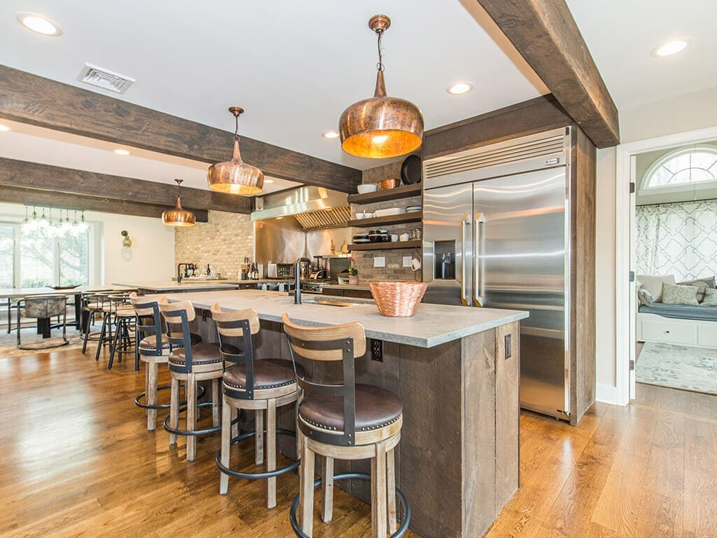 Rustic open floor plan kitchen, concrete island and peninsula, open shelving with exposed brick, industrial appliances, wood beams and hardwood flooring throughout in Rockaway, NJ remodeled by JMC Home Improvement Specialists