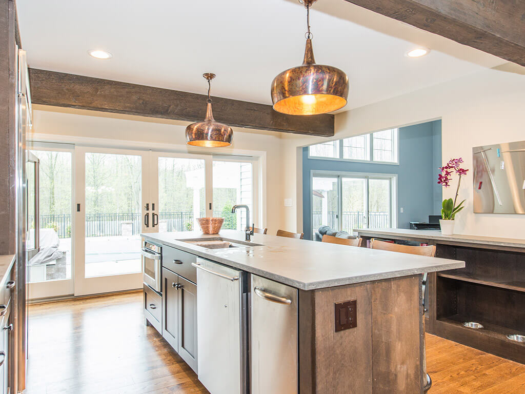Rustic open concept kitchen, concrete island, built in dog dishes, wood beams and hardwood flooring throughout in Rockaway, NJ remodeled by JMC Home Improvement Specialists