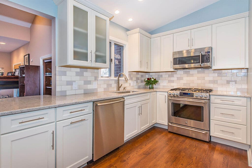 White Shaker cabinets with subway tile backsplash and hardwood floors in Summit, NJ remodeled by JMC Home Improvement Specialists