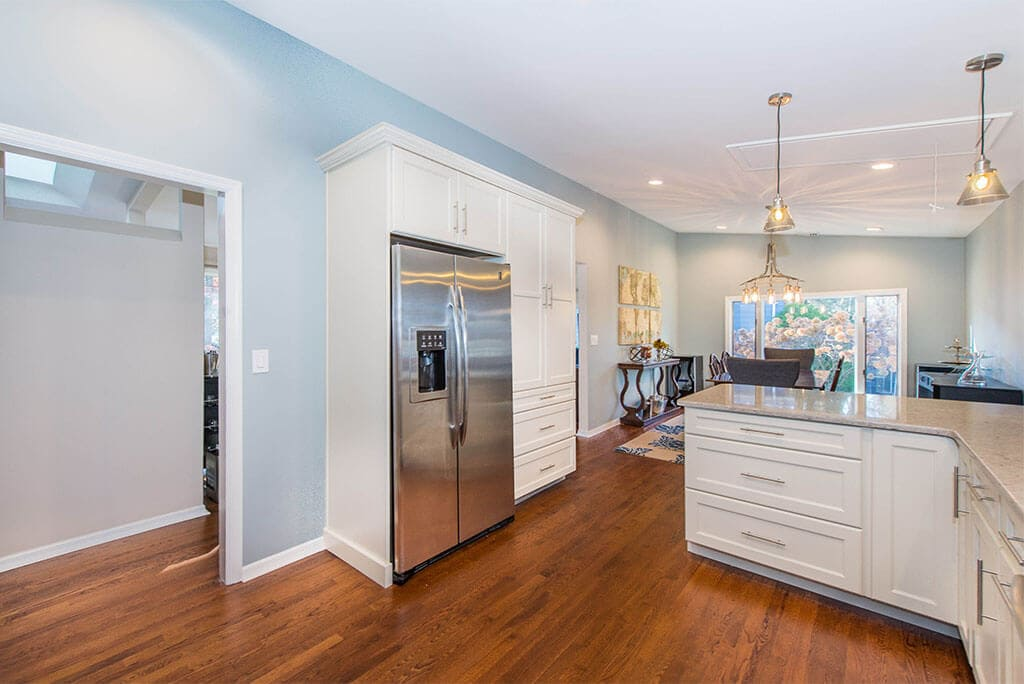 Open floor concept kitchen with white Shaker cabinets with subway tile backsplash and hardwood floors in Summit, NJ remodeled by JMC Home Improvement Specialists