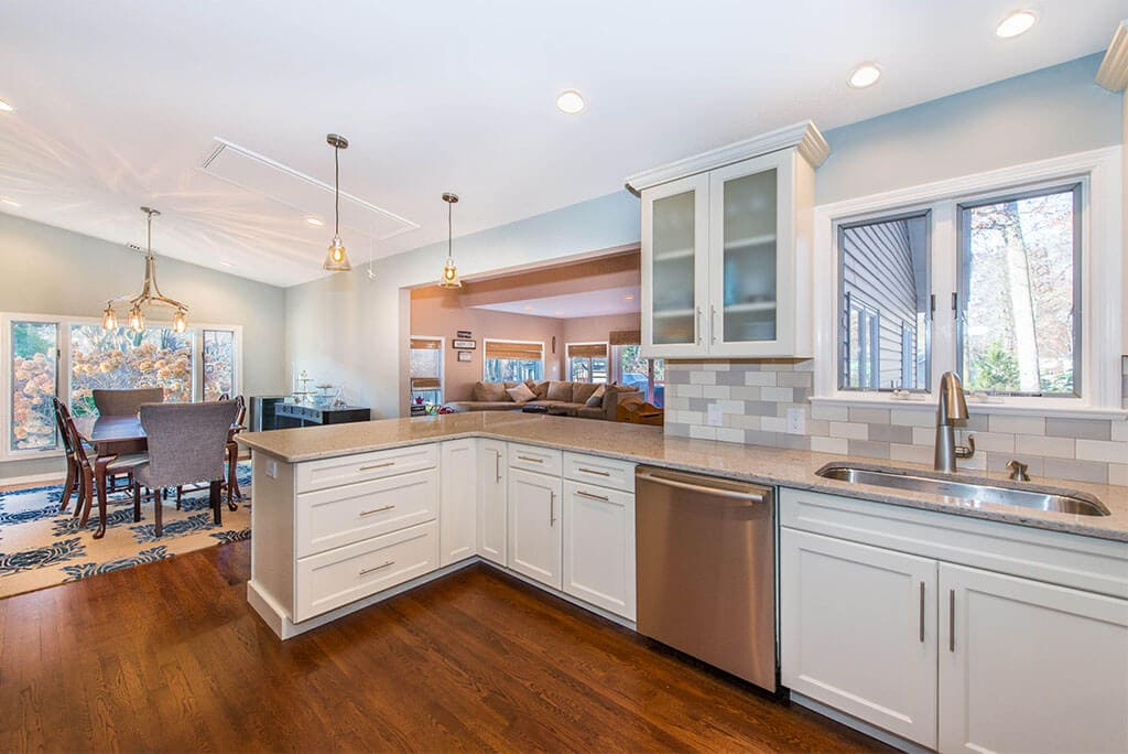 Wall removal for open floor concept kitchen with white Shaker cabinets and frosted glass cabinets with subway tile backsplash, pendant lighting and undermount stainless sink with hardwood floors in Summit, NJ remodeled by JMC Home Improvement Specialists