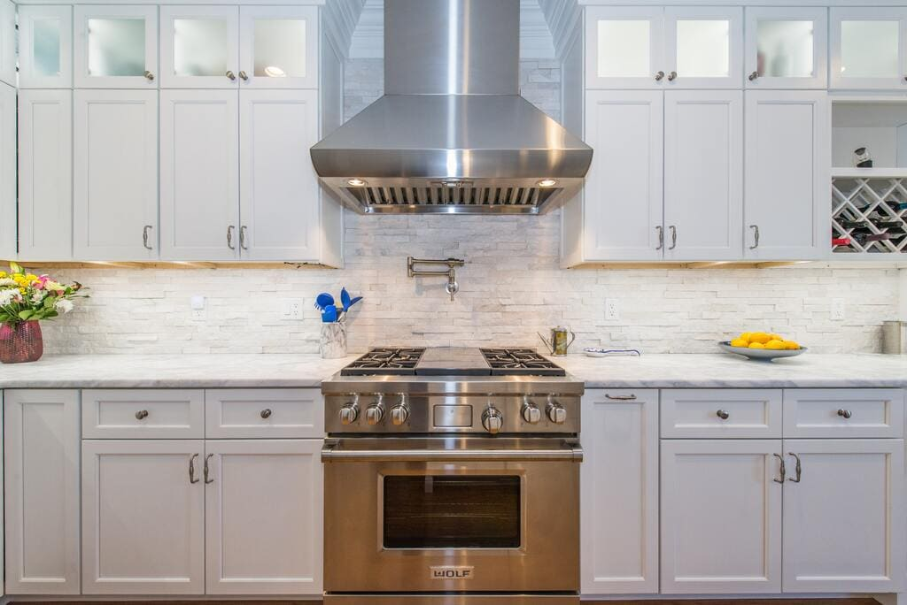 Double stack white shaker cabinets with frosted glass with metal freestanding hood and pot filler in Morristown, NJ remodeled by JMC Home Improvement Specialists