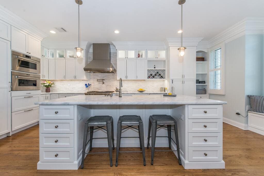 White kitchen with shaker cabinets and crown molding, marble countertops with pendant lights in Morristown, NJ remodeled by JMC Home Improvement Specialists