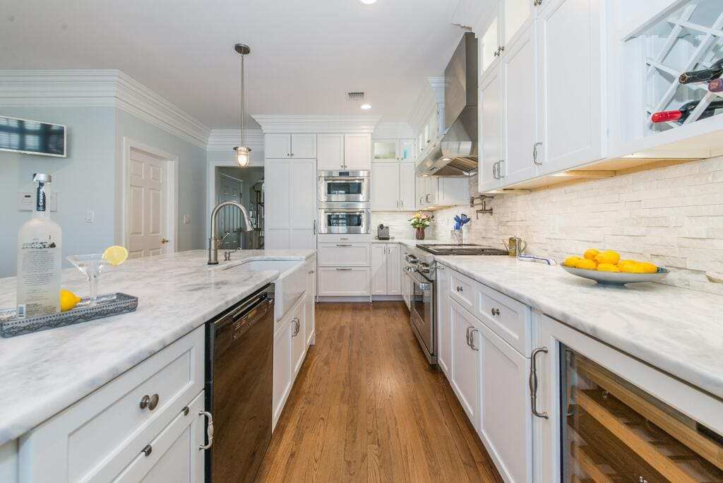 White kitchen with shaker cabinets and crown molding, marble countertops with farm sink, double ovens and panel fridge in Morristown, NJ remodeled by JMC Home Improvement Specialists