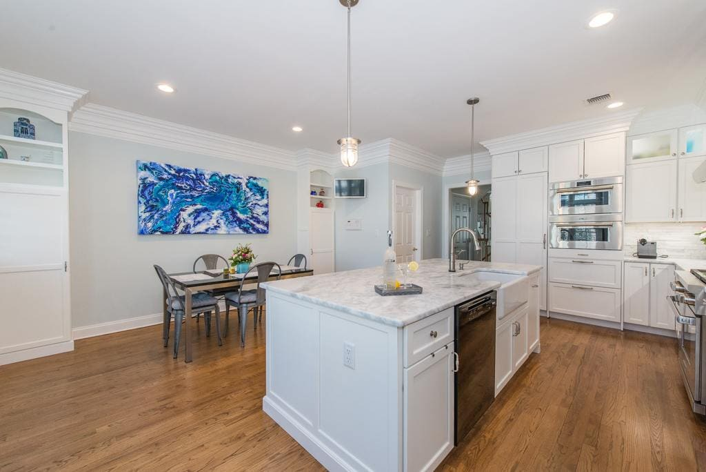 White kitchen with shaker cabinets and crown molding, marble countertops with farm sink, double ovens and panel fridge and freezer drawer in Morristown, NJ remodeled by JMC Home Improvement Specialists