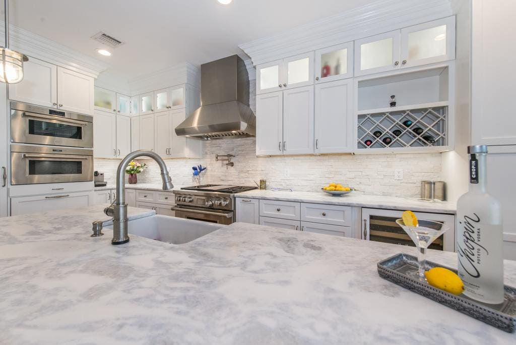 White kitchen with shaker double stack cabinets with frosted glass and crown molding, wine rack, marble countertops with farm sink in Morristown, NJ remodeled by JMC Home Improvement Specialists